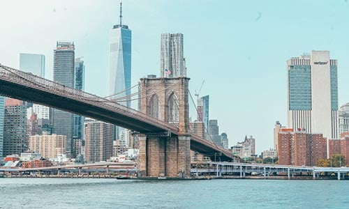 The Brooklyn Bridge stretches across the Hudson River with the New York City skyline on the far bank.