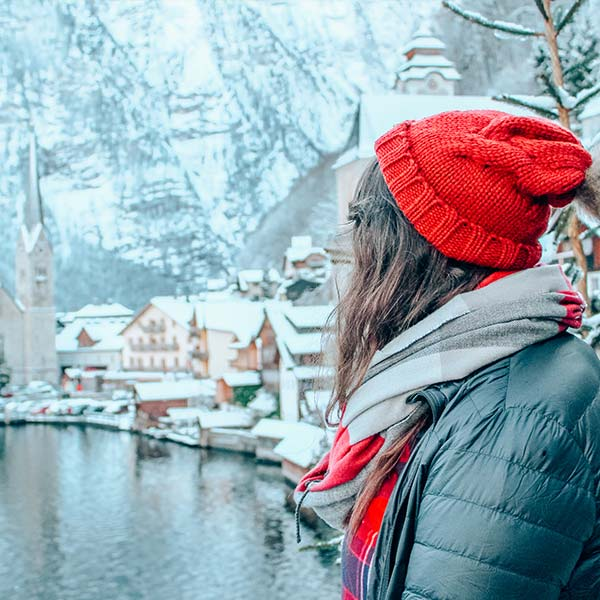 Girl in a red hat lookin out over snowy rooftops in Hallstatt, Austria