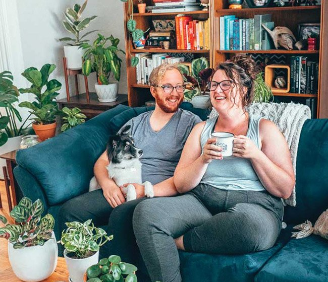 Couple on a blue couch surrounded by plants, holding a fluffy black and white dog and laughing