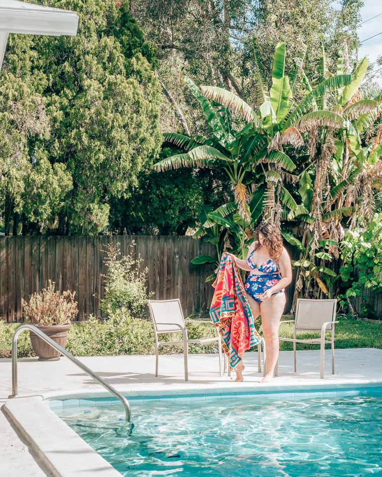 Girl in swimsuit with a towel in front of banana trees at a pool