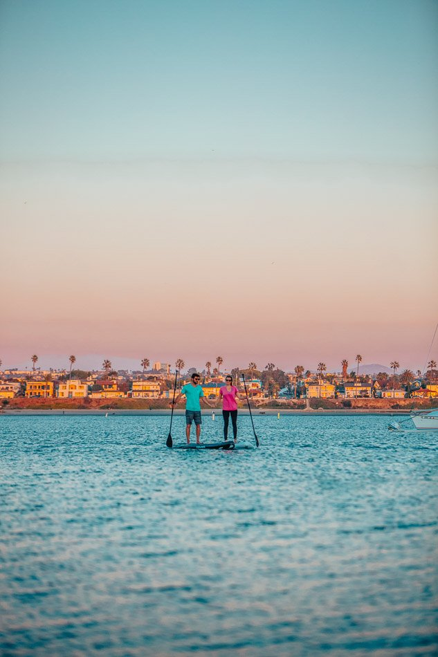 Couple paddle boarding together on the bay during sunset in San Diego, CA.