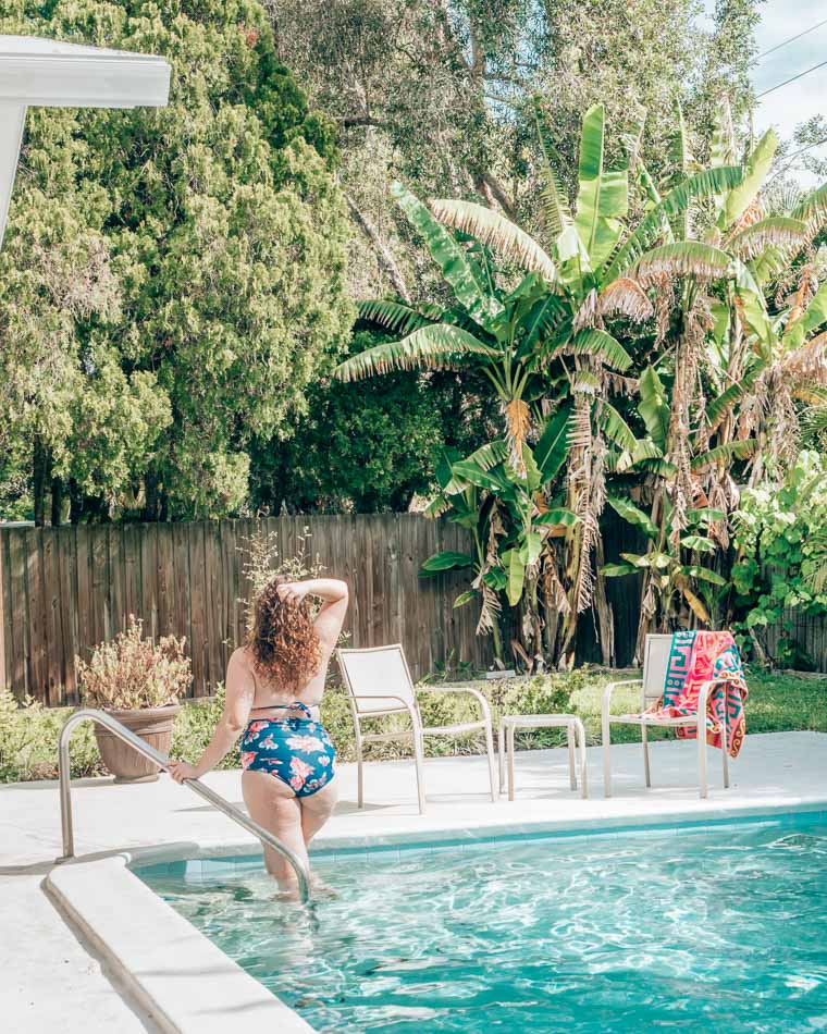 Girl in blue swimsuit getting out of a pool in front of banana trees