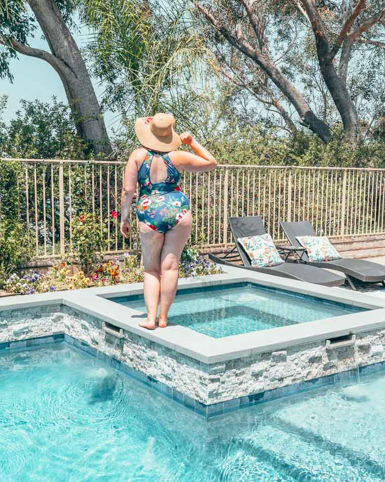 Curvy girl in a blue swimsuit shown from behind wearing a star sun hat and posing on the edge of a swimming pool