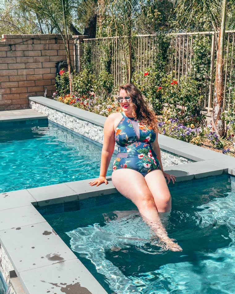 Plus sized girl in a blue bathing suit sitting on the side of a swimming pool