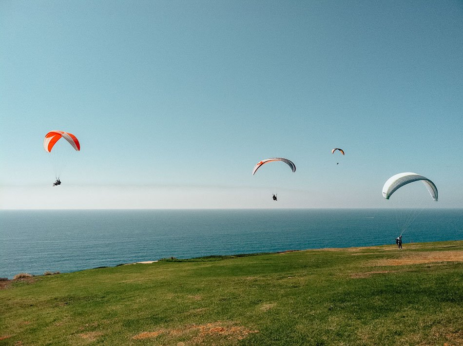 People paragliding at Torrey Pines Gliderport during a nice day in San Diego CA.