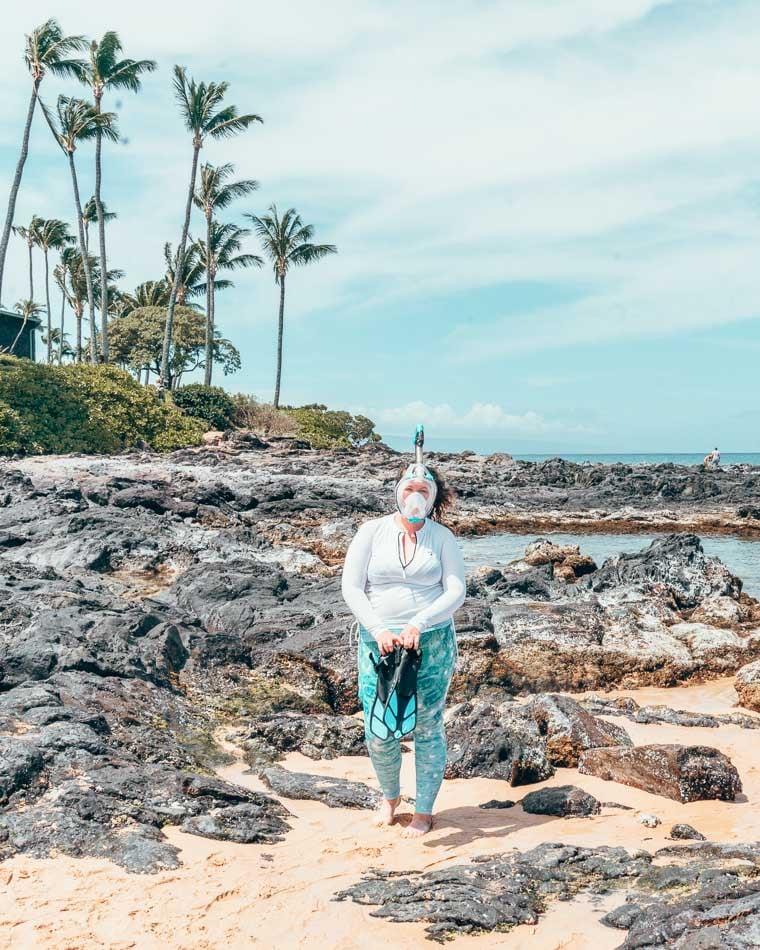 Girl in snorkel gear and swim leggings in front of black volcanic rock.