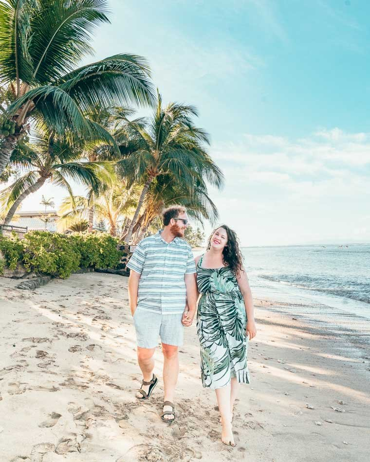 Travel blogging couple Lia and Jeremy holding hands and walking on a beach in Maui, Hawaii