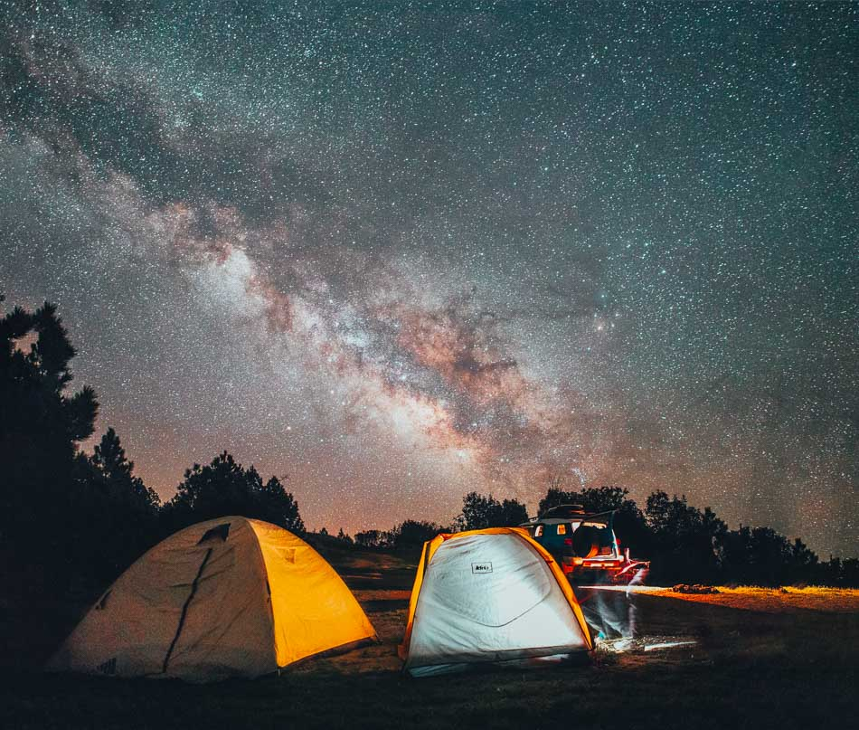 Camping in tents at night with views of the milky way in Big Sur, CA.