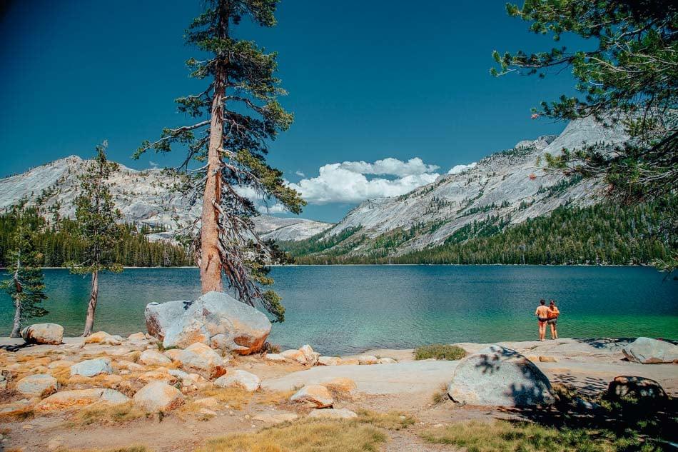 Couple taking in the view up close of Tenaya Lake at Yosemite National Park, CA