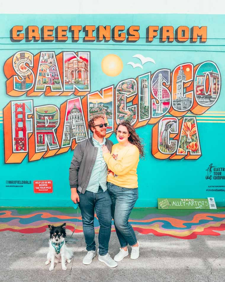 """Lia, Jeremy, and Mulan in front of the """"Greetings from San Francisco"""" street art mural in San Francisco, California!"""
