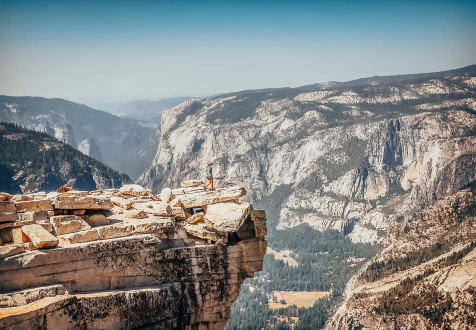 Hiker at the edge of a cliff taking in the view at the top of Half Dome in Yosemite, CA