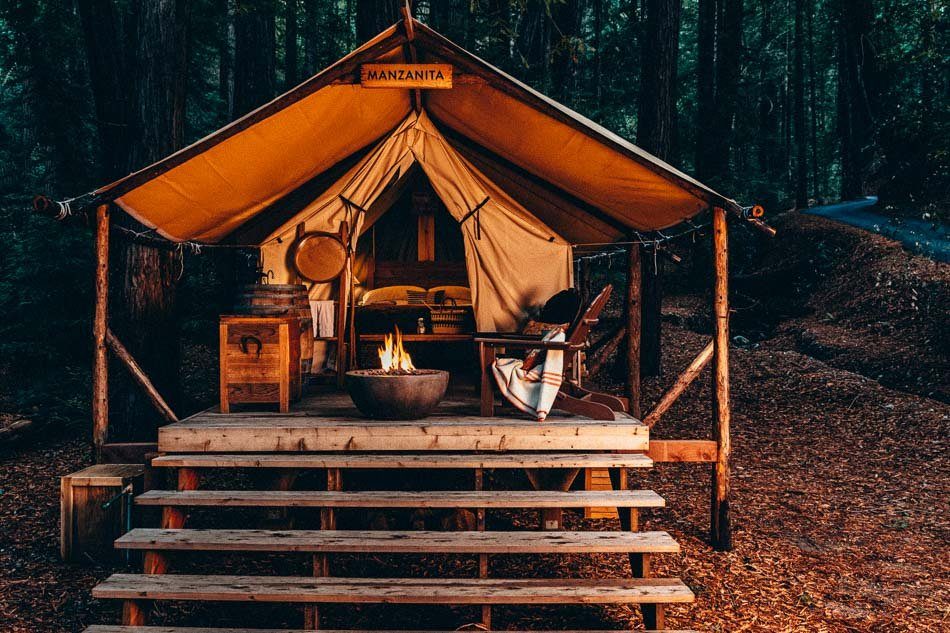Outdoor cabin set up at the Hilton Resort during nighttime with a fire place