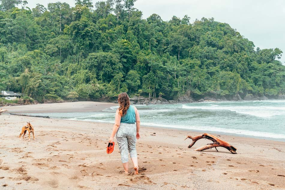 Lia Walking on Beach in Corcovado National Park Costa Rica carrying a pair of shoes