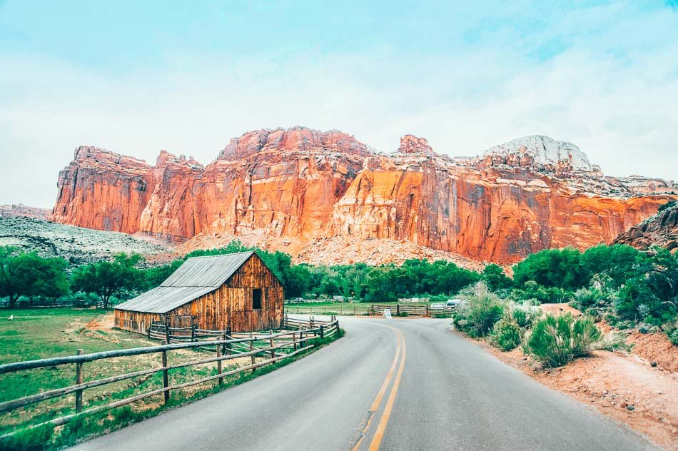 A road going by a barn and leading to a canyon in the background in Fruita at Capitol Reef National Park in Utah