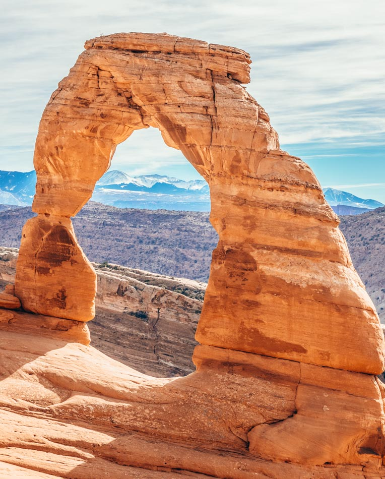 The distinct single arch with mountains in the background at Arches National Park in Utah