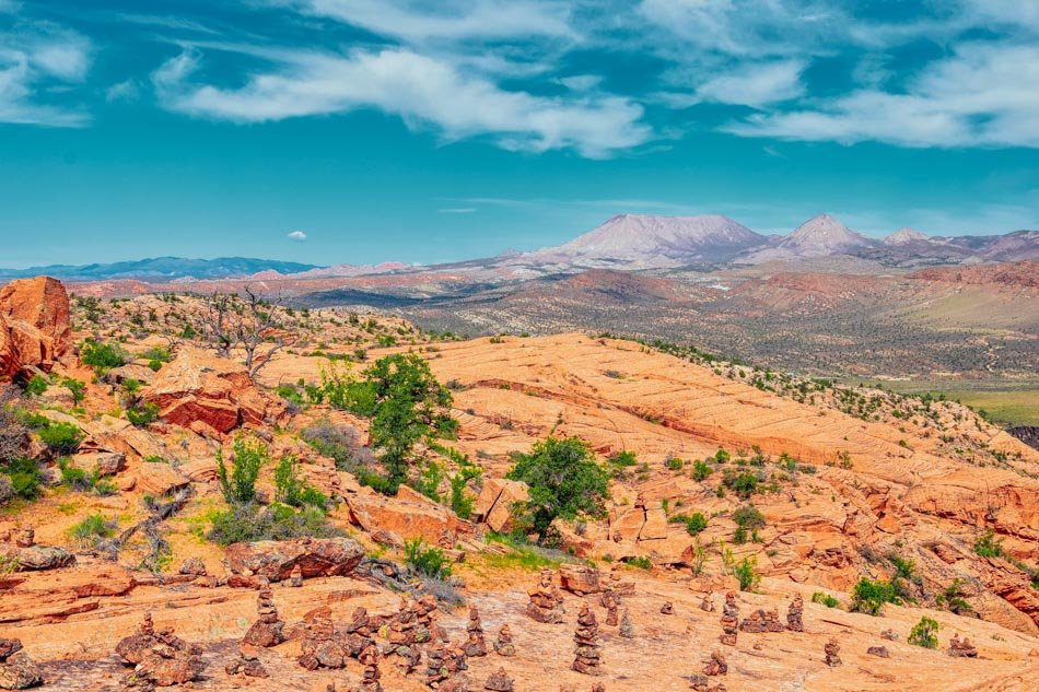 A sweeping view of Snow Canyon State Park with mountains in the background in Utah