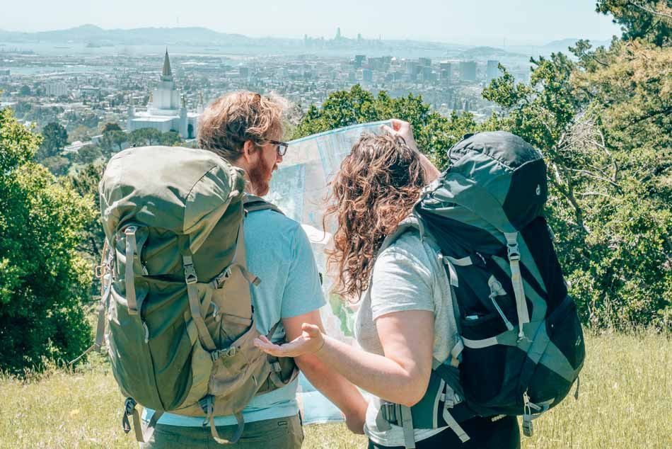 Couple travel bloggers looking at a map wearing backpacks.