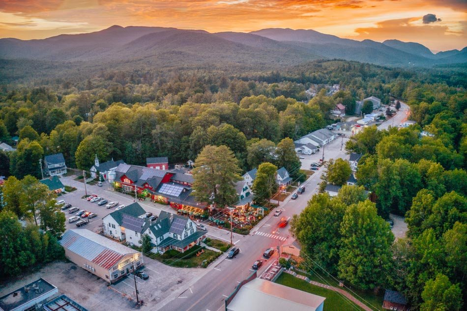 An aerial view of the town of Woodstock at sunset with the mountains in the background in Woodstock, New Hampshire