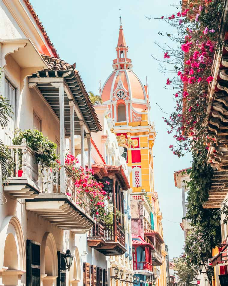 Flower-covered balconies in the foreground lining a street, with the yellow and pink tower of Cartagena, Colombia's cathedral rising above.