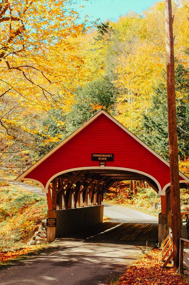 A red wooden covered bridge over Pemigewasset River surrounded by fall foliage in Lincoln, New Hampshire