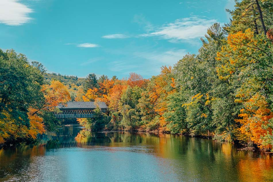 A wooden covered bridge over a river surrounded by fall foliage in New Hampshire