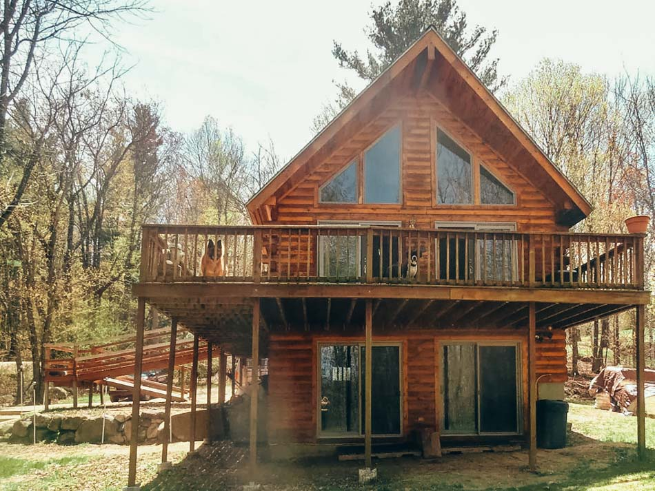 The exterior of a cozy wooden A-line cabin in New Hampshire