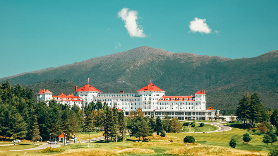 The white exterior of the Mount Washington Hotel with the White Mountains in the background in New Hampshire