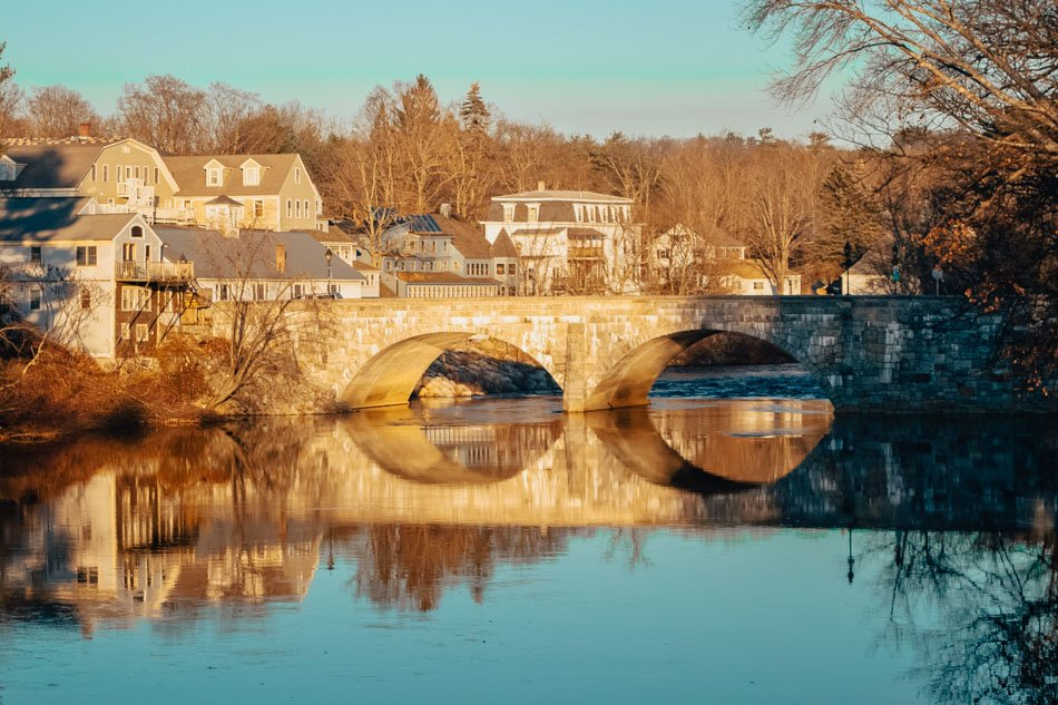 A historical stone bridge over a river with downtown Henniker in the background in Henniker, New Hampshire