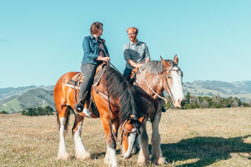 Lia and Jeremy riding Clydesdale horses in Cambria, California on the Central Coast