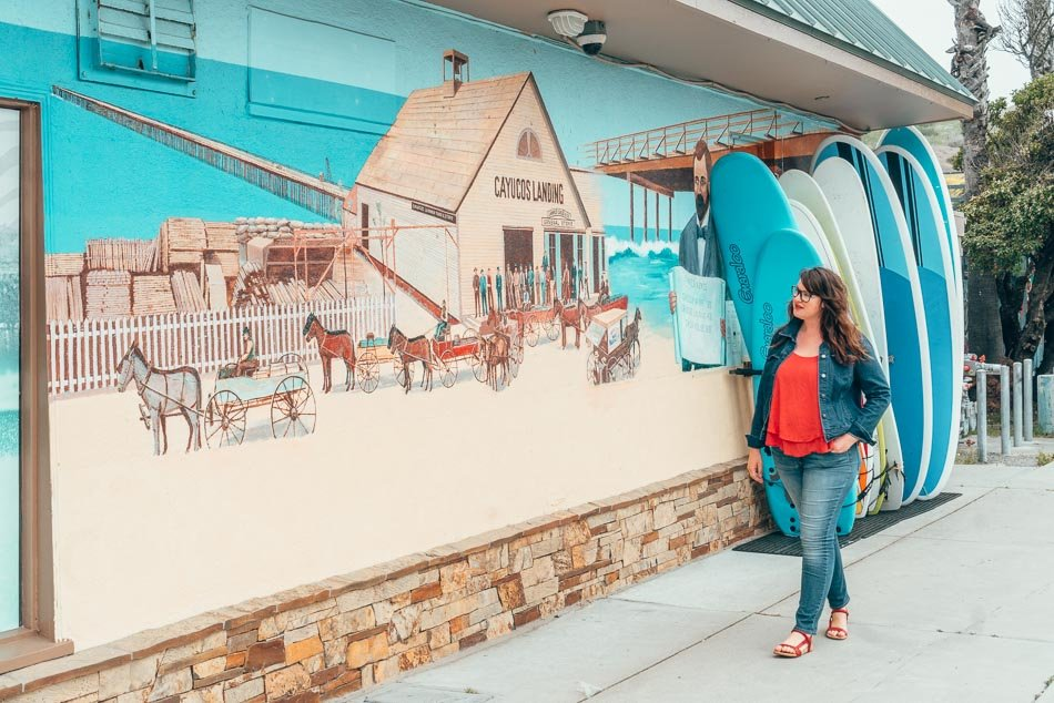 Lia in front of a mural with horses and wagons with surfboards again it in Cayucos, California on the Central Coast