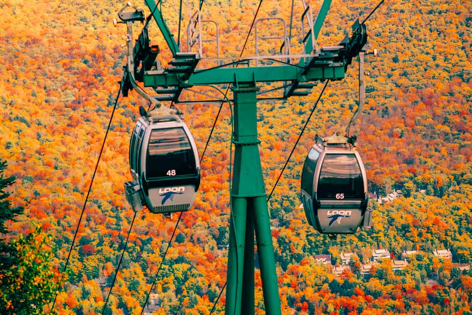 Gondolas going up Loon Mountain overlooking the fall foliage in New Hampshire