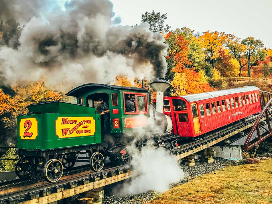The Mount Washington Cog Railway with a steam engine and lots of steam surrounded by fall foliage in New Hampshire