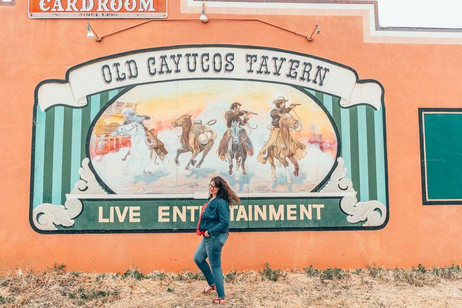 Old Cayucos Tavern mural with horses in it with Lia standing in front of it in Cayucos, California on the Central Coast