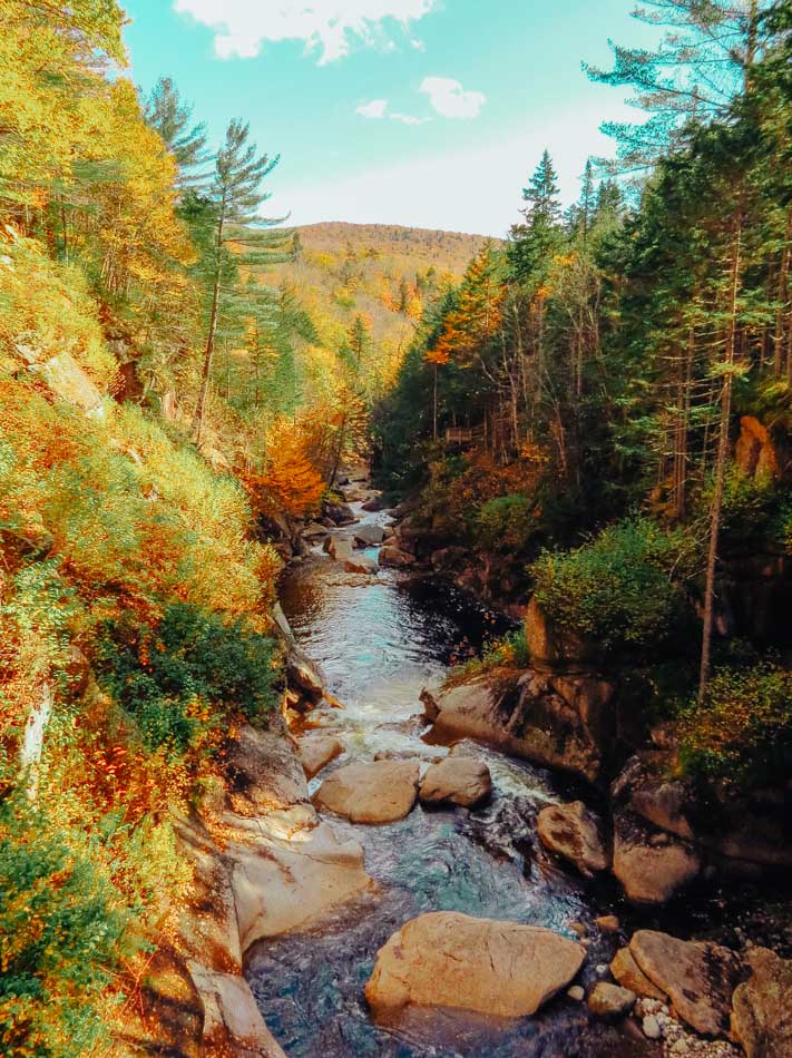The Pemigewasset River flowing through the Flume Gorge with fall foliage in Lincoln, New Hampshire