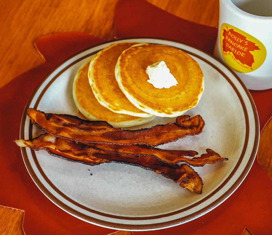 A plate of pancakes with bacon and a coffee mug at Polly's pancake Parlor in Sugar Hill, New Hampshire