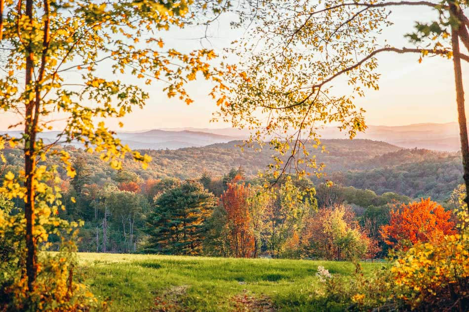 A scenic view at sunset of the rolling hills and forest with fall foliage in Walpole, New Hampshire