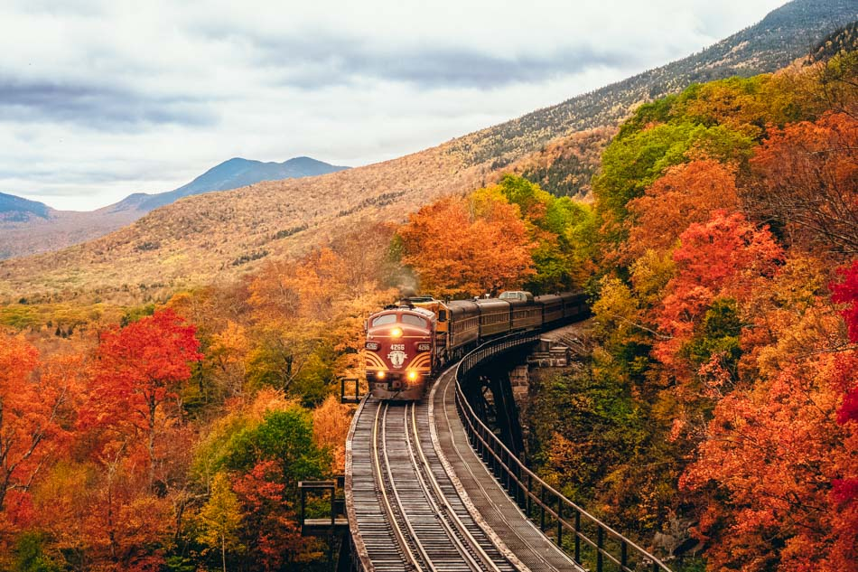 A train on a wooden bridge going through the fall foliage in New Hampshire